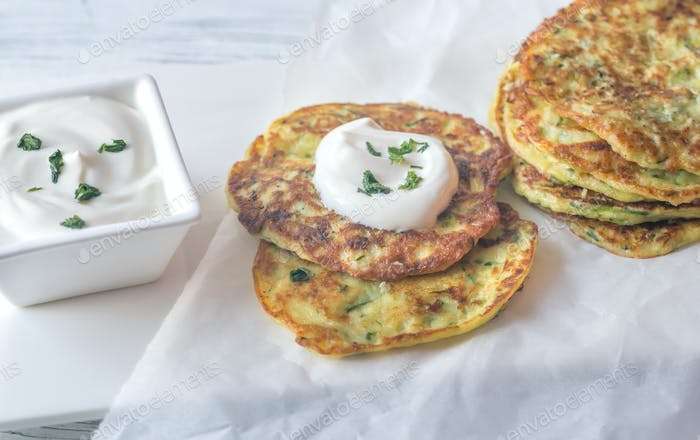Portion of zucchini fritters with greek yogurt