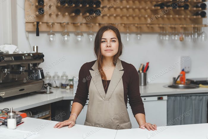 Vertical de una joven camarera en la cafetería detrás del mostrador.