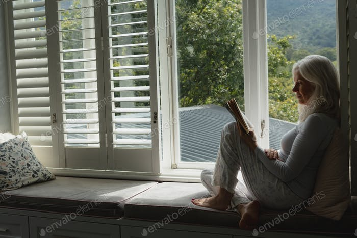 Side view of active senior Caucasian woman reading a book on window seat at home