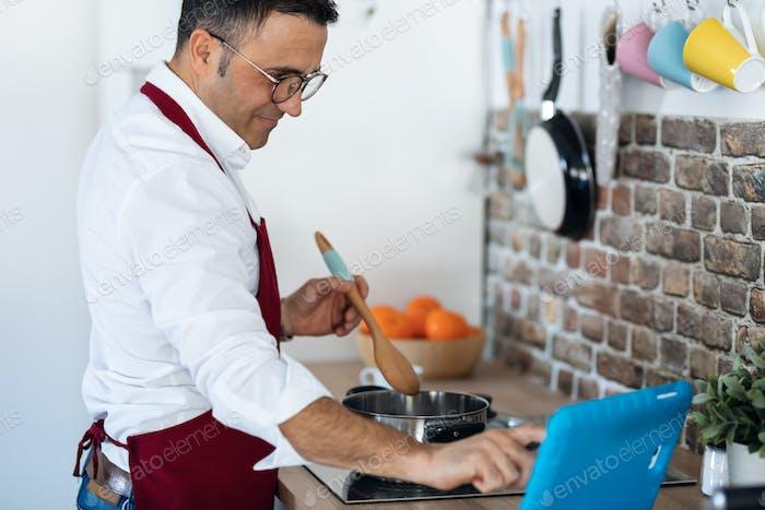 Schöner Mann kochen, während nach einem Rezept auf dem digitalen Tablet in der Küche zu Hause.