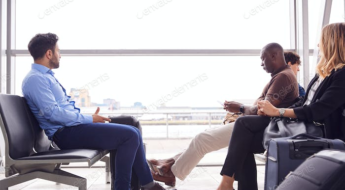 Business Passengers Sitting And Waiting In Airport Departure Lounge