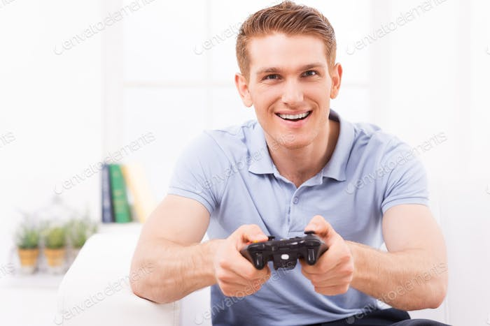 Man playing video game. Happy young man using joystick while playing video game at home