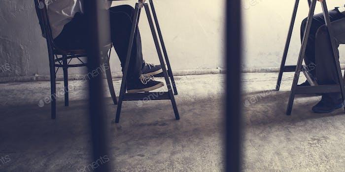 Closeup of pairs of legs in jail