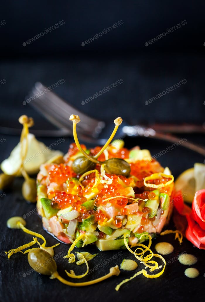 Delicious red caviar, salmon and avocado tartar