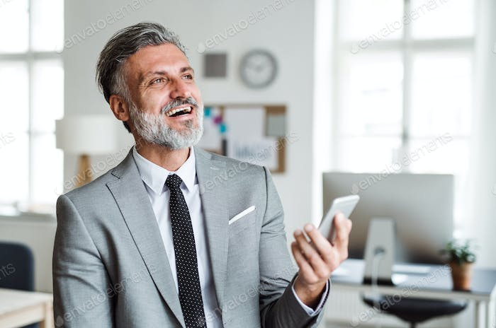Cheerful mature businessman with smartphone standing in an office, laughing.