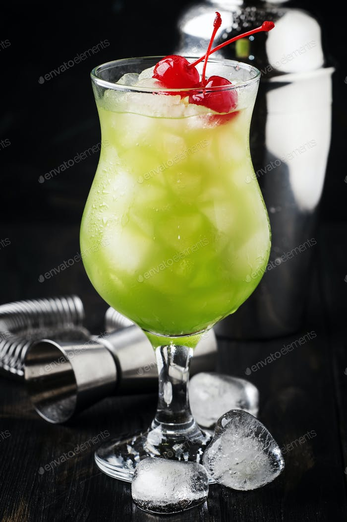 Grüner alkoholischer Cocktail mit Maraschinokirschen
