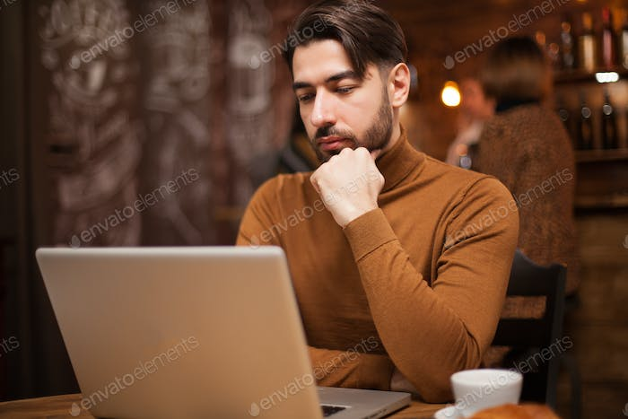 Stylish businessowman reading an email on his laptop while being in a coffee shop