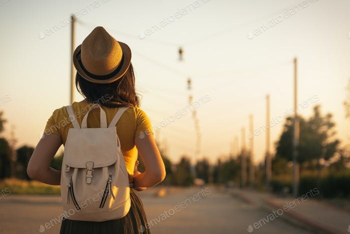 Back view of young woman looking the road.