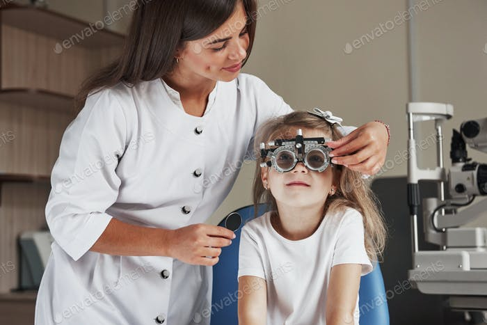 Now tell me what you see. Little girl in glasses sitting in clinic and having her eyes tested