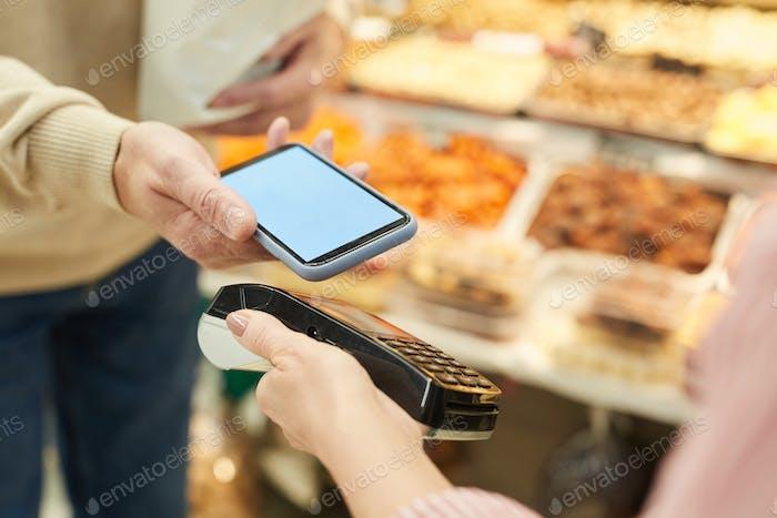 Cliente irreconocible que paga a través de NFC en Farmers Market