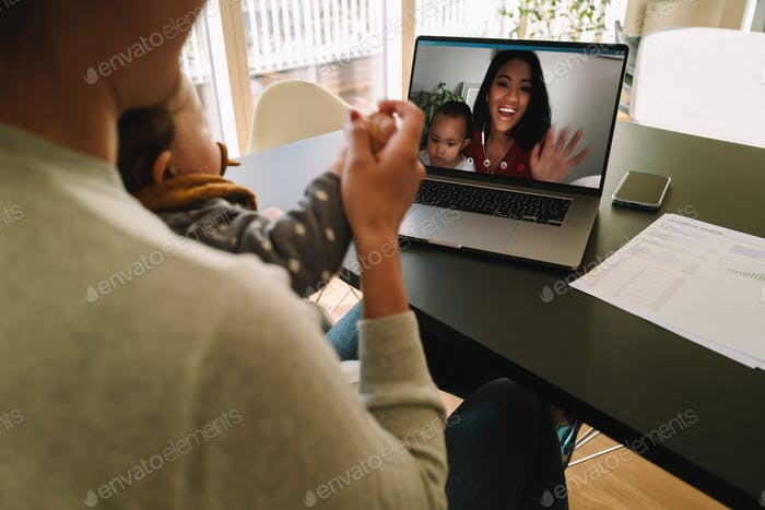 Women with their kids having a video call on laptop