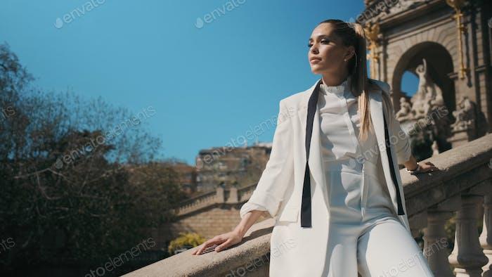 Элегантная женщина в классическом костюме уверенно позирует на лестнице в парке со старой красивой архитектурой
