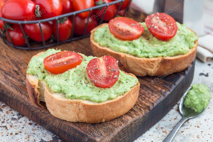 Open sandwich with mashed avocado and cherry tomatoes, sprinkled with black pepper, horizontal