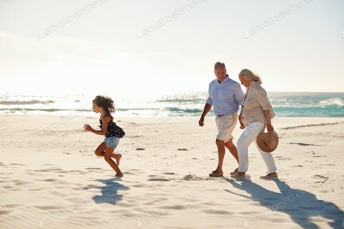 Senior pareja blanca y su nieta caminando en una Playa soleada, vista lateral