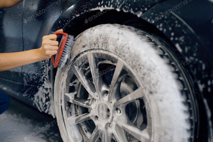 Female washer with brush cleans wheel, car wash