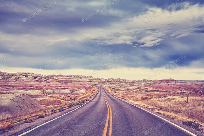 Color toned scenic road with moody sky, travel background.