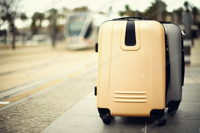 Citypass Light Rail in Jerusalem. Two suitcases standing on railway station against city train