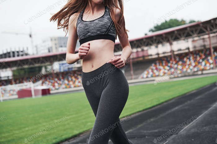 Picture in motion. Young blonde running on the track in the stadium at daytime