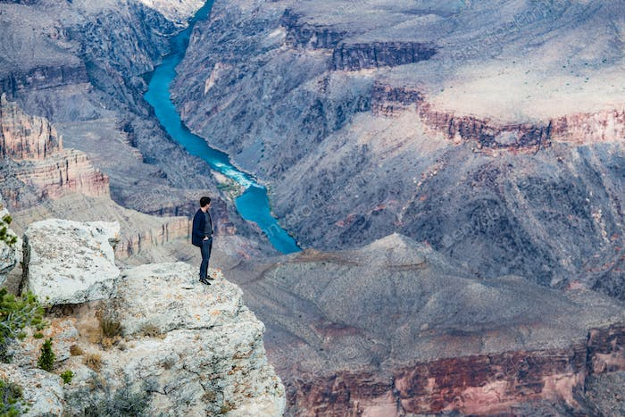 A Man Standing on the Rim of the Grand Canyon