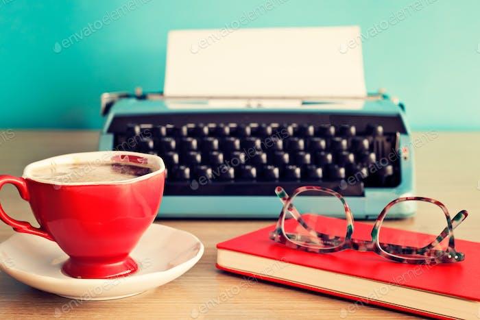Vintage typewriter, coffee cup and eyeglasses over red notebook