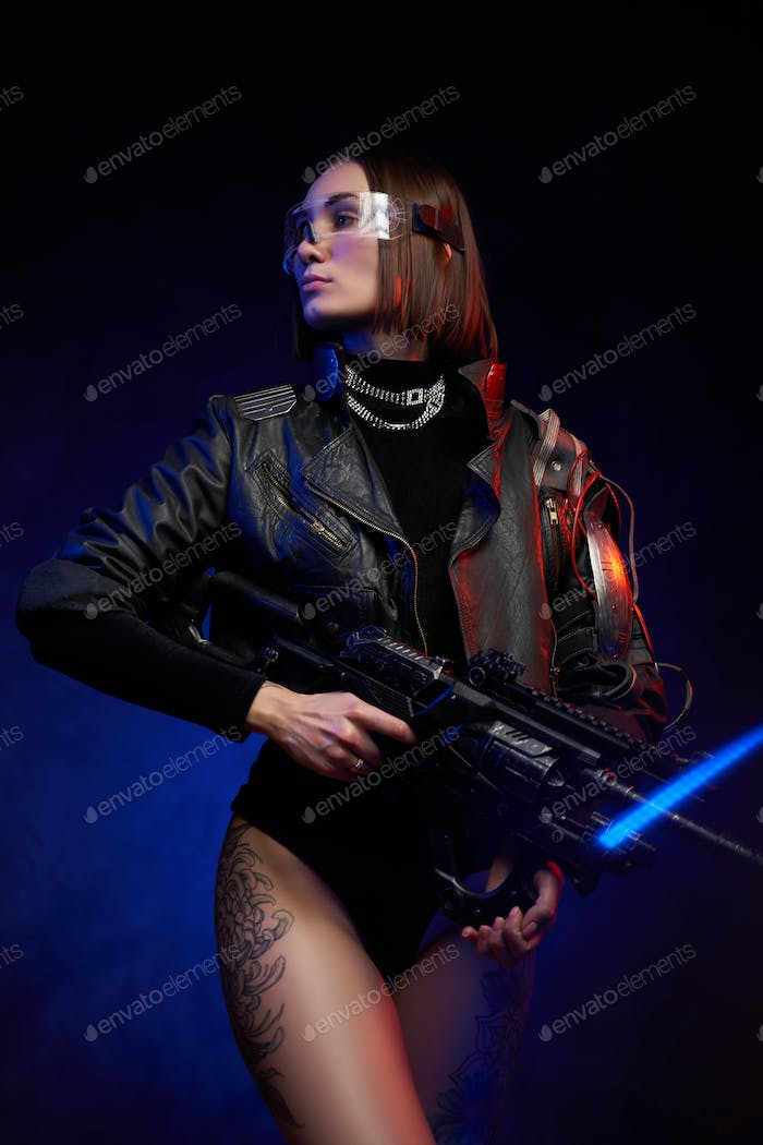 Military female person in black clothing holding rifle in studio