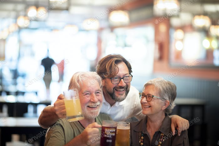 Happy cheerful senior family with son having fun while drinking beer together at restaurant