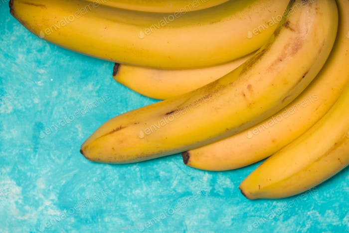 Whole bananas on a turquoise background free space