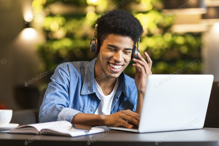 Cheerful teen guy with headset looking at laptop