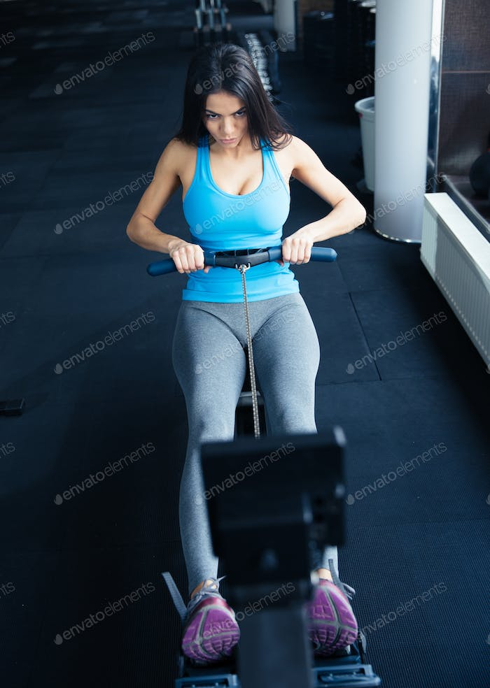 Young woman doing exercise on a simulator