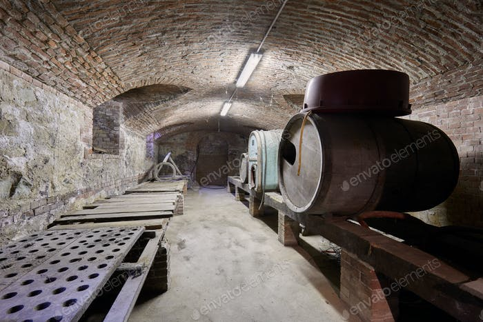 Old cellar with wooden barrels and brick ceiling