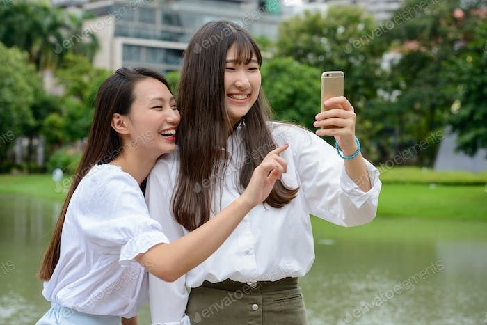 Thumbnail for Two happy young beautiful Asian teenage girls taking selfie together at the park