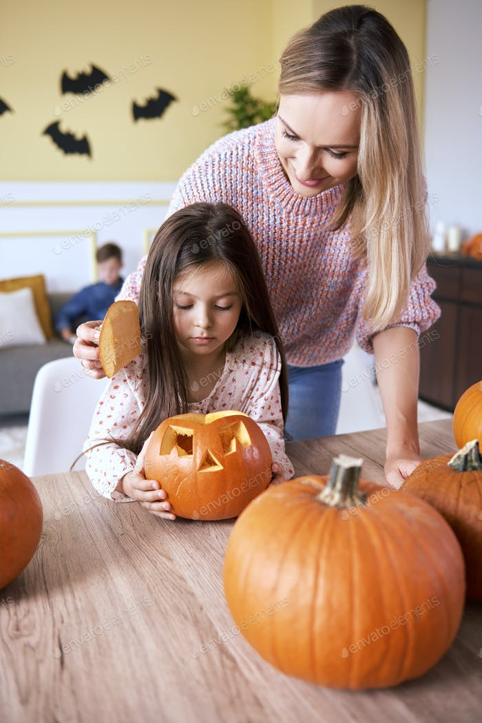 Girl carving pumpkin for Halloween