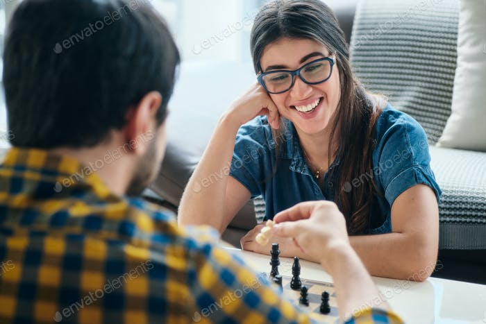 Young Woman Playing Chess Game With Boyfriend