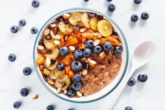 chocolate oatmeal porridge with blueberry, nuts, banana, dried a