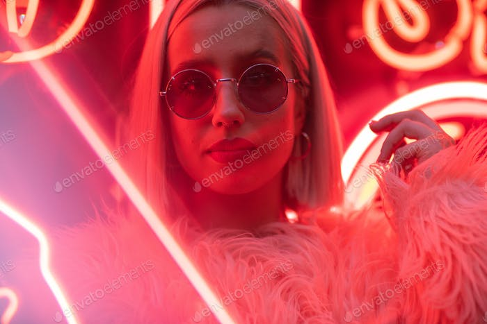 Cinematic portrait of blond girl with furry pink coat on neon sign at night