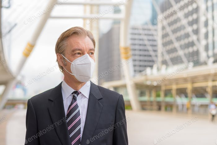 Face of mature businessman wearing mask and thinking at skywalk bridge