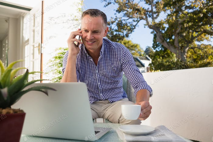 Geschäftsmann am Telefon sprechen, während Kaffee im Café im Freien