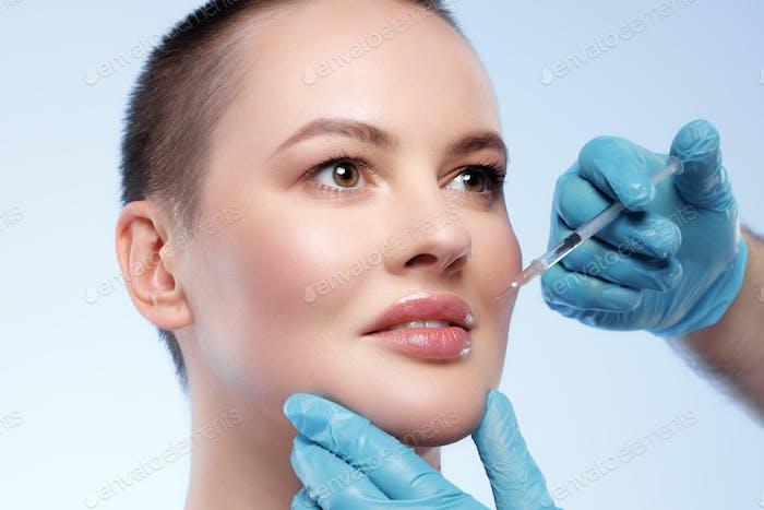 Hermosa mujer con el pelo corto consigue una inyección de belleza en su cara
