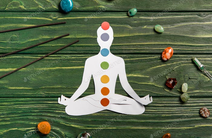top view of paper figure in form of person with chakras in lotus pose, aroma sticks and colorful