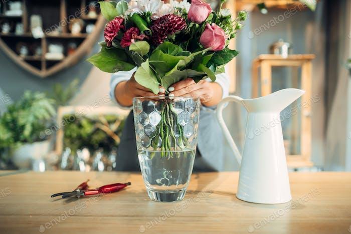 Female florist puts flower bouquet into a vase