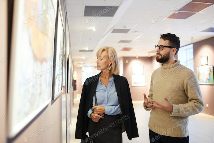 Mature Couple Looking at Paintings in Art Gallery