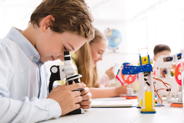 Smart schoolboy looking at microscope with robot nearby