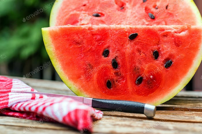 Big slice of fresh watermelon on wooden table