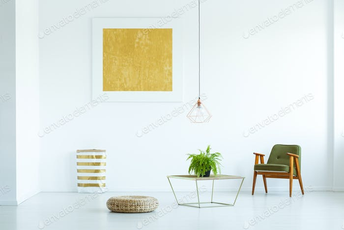 Table with plant between pouf and green armchair in white flat i