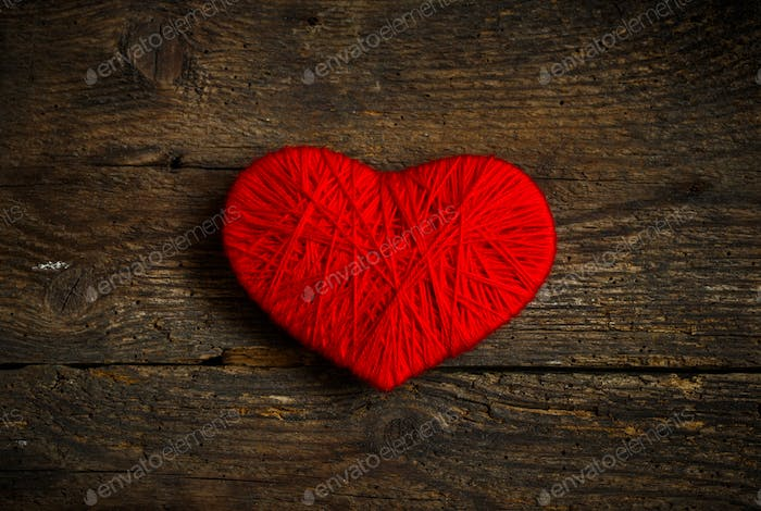 Red heart shape made from wool on old shabby wooden background