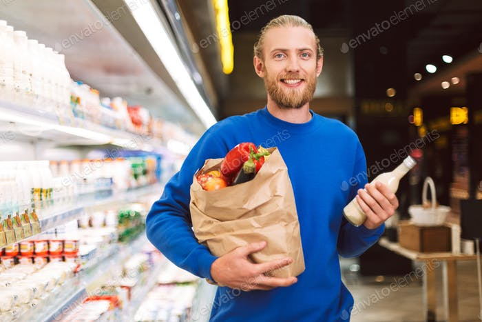 Young smiling guy in dark blue sweater holding paper grocery bag