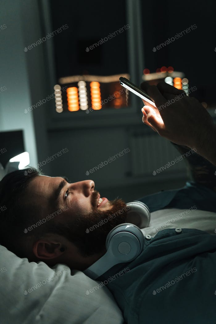 Smiling young bearded man laying on bed at home