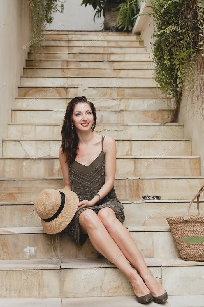 young stylish attractive woman in elegant dress sitting on stairs, straw hat and bag