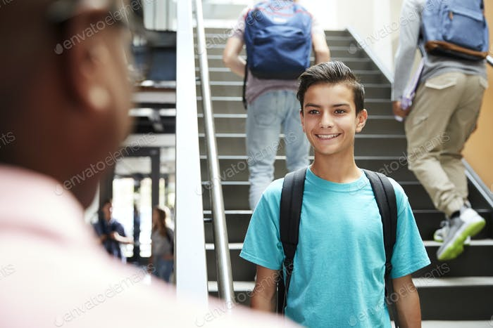 Male High School Student Talking With Teacher In Busy Corridor