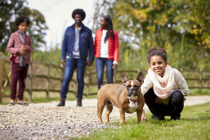 Mixed race girl squatting to pet her dog during a family walk in the countryside